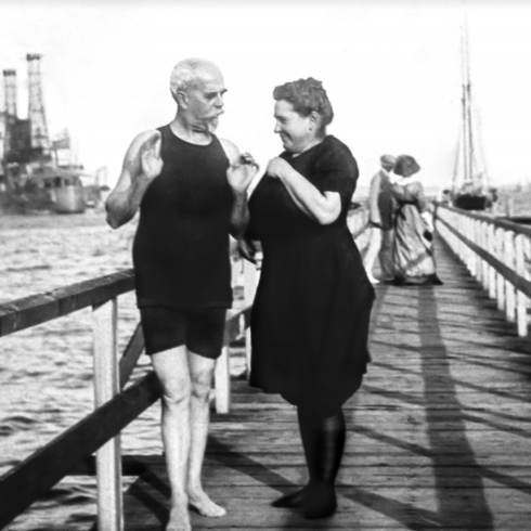 Black and white photo of man and woman on boardwalk.