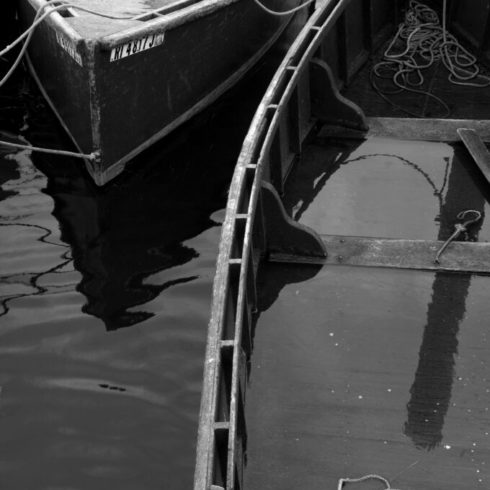 Black and white photo of 2 small rowboats.