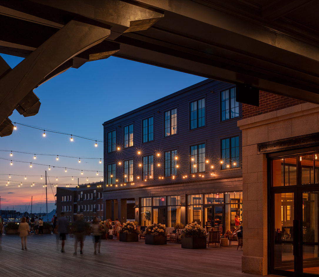 Outdoor dining decorated with string lights at sunset.