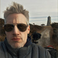 Headshot of man with lighthouse in the background.