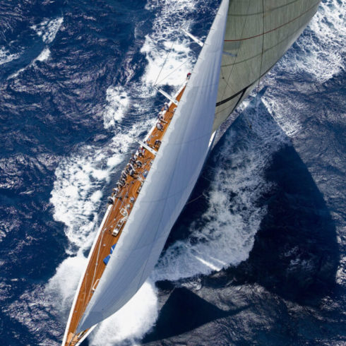 Birds-eye-view of white sailboat in the ocean.