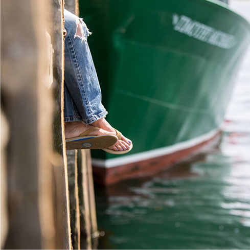 Person's legs hanging over the water.