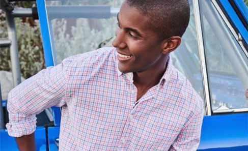 Man smiling, leaning against blue car.