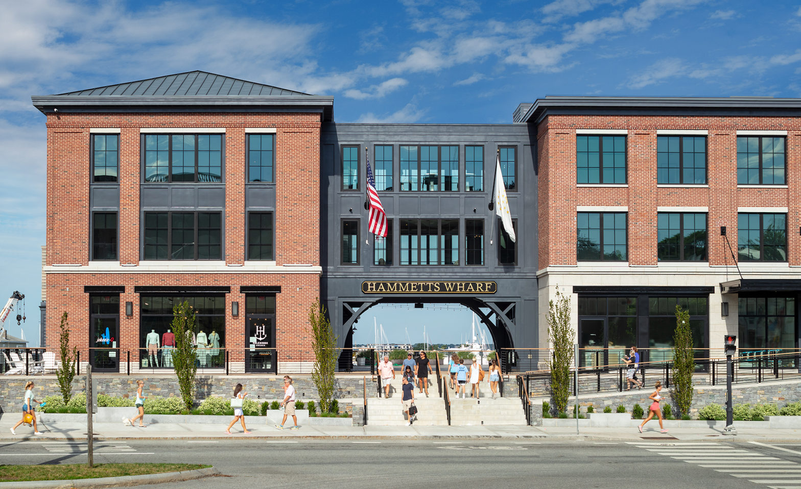 Front view of Hammetts Wharf building with pedestrians walking/shopping.