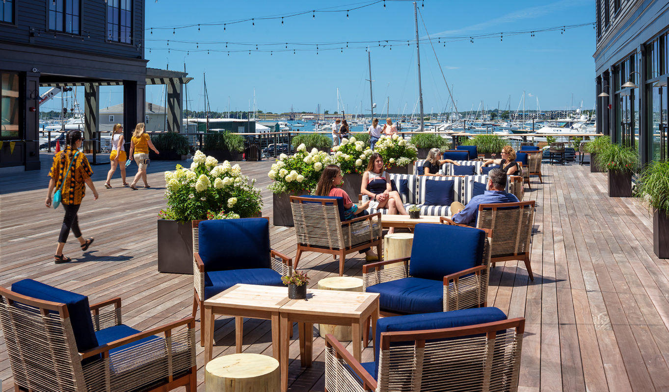 Deck seating area with lots of flowers and a view of the marina.