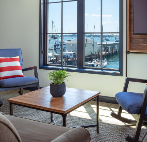 Two chair seating area inside with a view of the harbor.