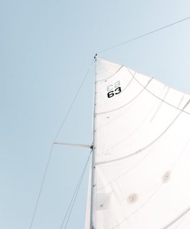 Ground view of a big white sailboat sail, with a blue sky.