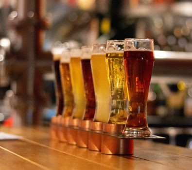 Seven different types of beers in beer glasses, lined up on bar.